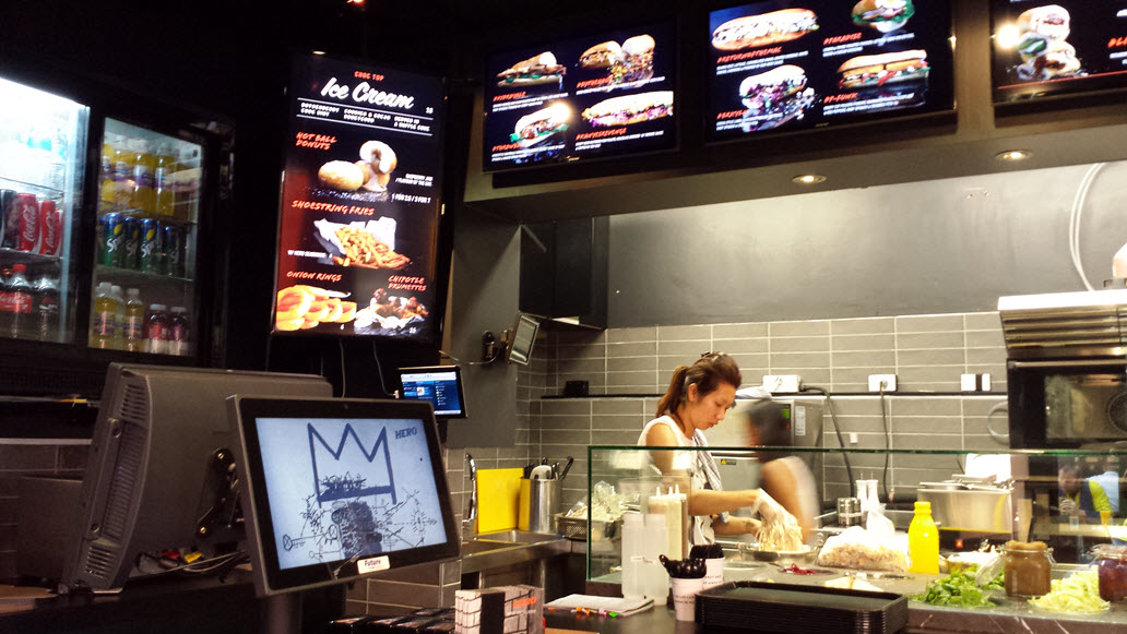 The Hardware Lane location in Victoria. Pictured from left to right is the customer-facing signage including a real-time scoreboard which displays the customer order as its rung in, as well as the digital menuboards which display Hero Subs's extensive menu in high definition.